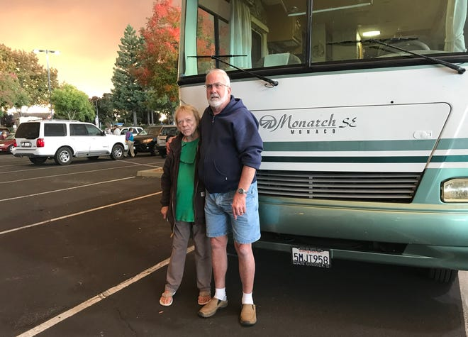 Jane Latham and Ed Van Der Linden stand in front of their motorhome in the Chico Mall parking lot. The couple rescued others from the Camp Fire on Thursday.