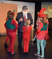 "Kris Kringle (David Cutler) confers with some Macy's department store elves in a scene from ""Miracle on 34th Street."" The Christmas classic opens Friday at Riverfront Playhouse."