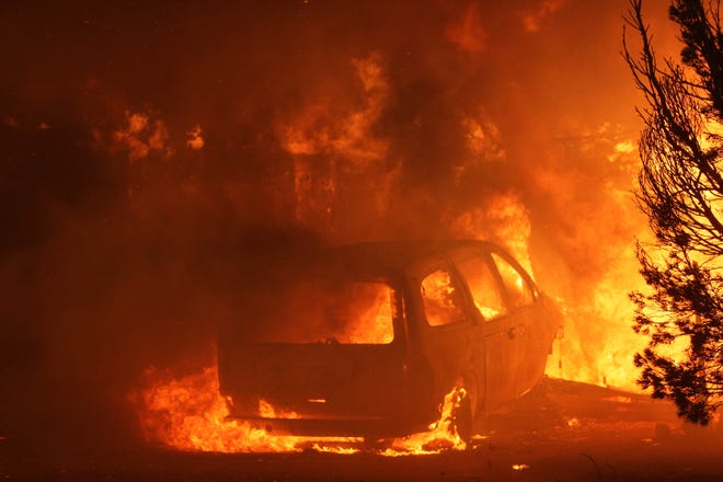 The Camp Fire burns a car Thursday night on the west side of Skyway about 2 miles north of Highway 99 east of Chico.