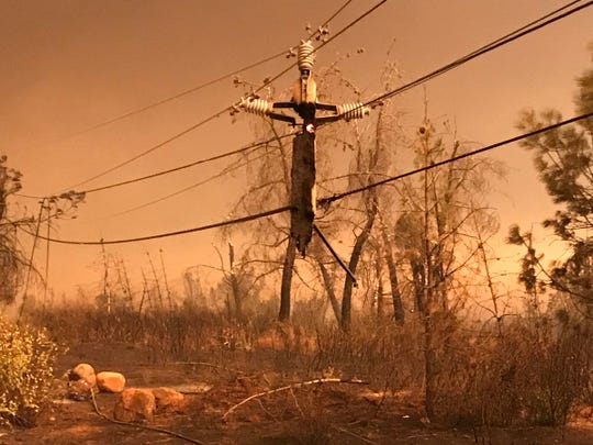 Remnants of a telephone pole hang from their lines after they burned in the Camp Fire on Thursday, Nov. 8, 2018.
