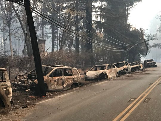 Abandoned and charred vehicles line a road in Paradise Friday after the Camp Fire destroyed the area on Thursday.