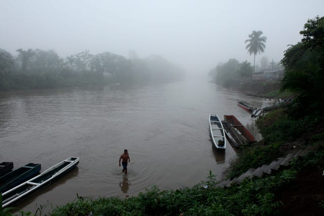 In this June 22, 2012, file photo, a man bathes in a river at dawn in the Darien Province on the border with Colombia, in Union Choco, Panama. One man's journey to America from his home in Mauritania was a dangerous and arduous one that took him through the Darien Gap.