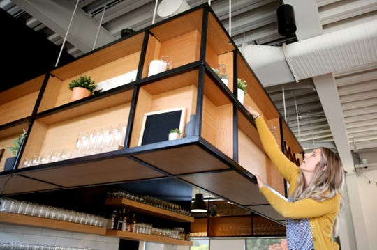 Amy Kaufman designs a shelf space that hangs above the bar at Basil & Board in downtown Salem on Friday, Nov. 9, 2018. The restaurant is set to open soon.