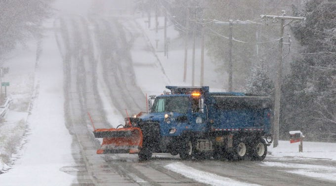 A City of Sheboygan snow plow truck turns north onto South 12th Street, Friday, November 9, 2018, in Sheboygan, Wis. Snow reduced visibility and produced challenges for motorists.