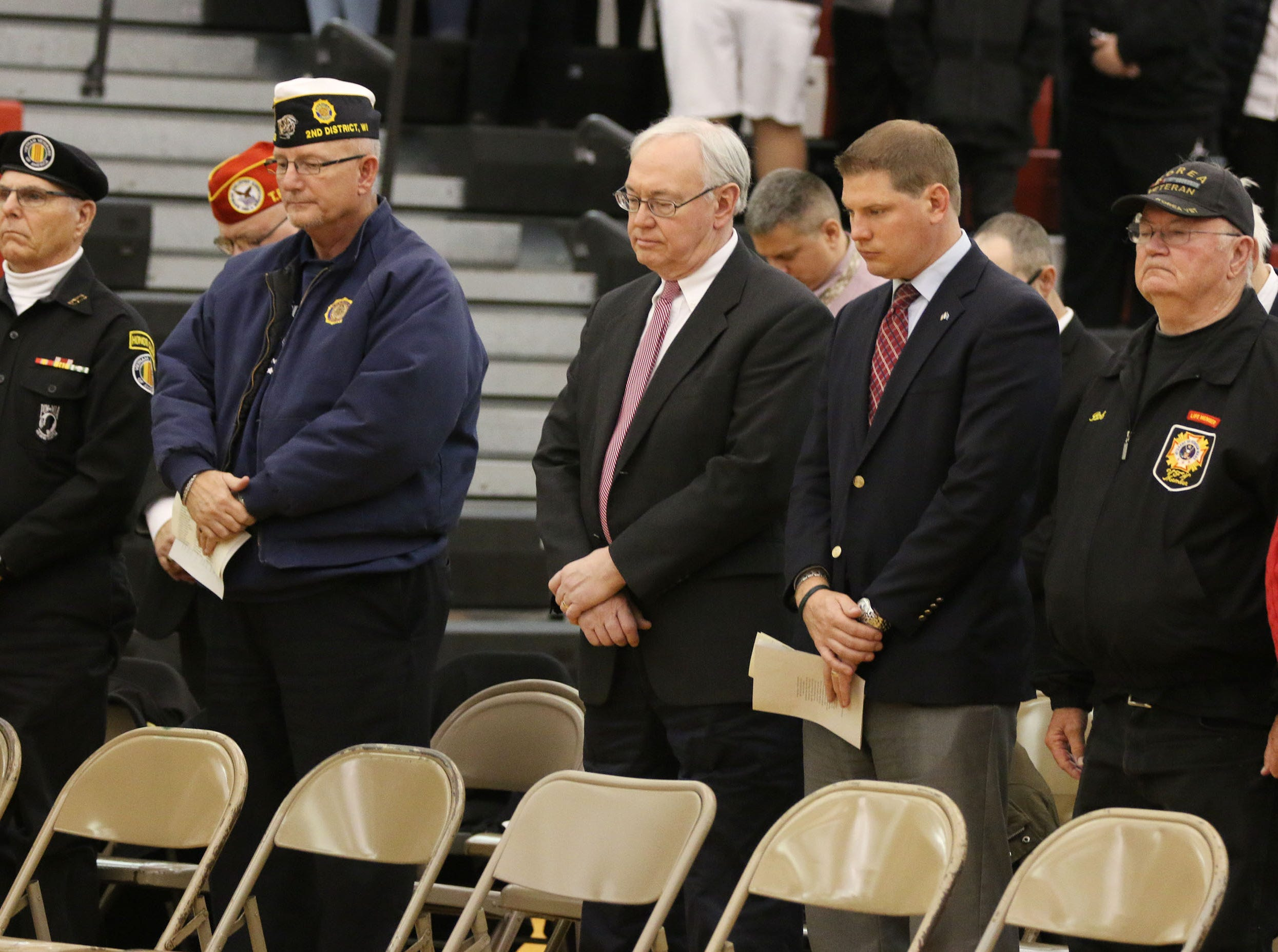 Dignitaries stand during a moment of silence at the Sheboygan South Veterans Day Program, Friday, November 9, 2018, in Sheboygan, Wis.
