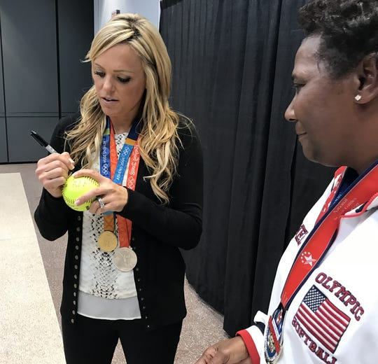 Former professional softball pitcher Jennie Finch signs a softball for SportsWorld employee Shirley Snell.