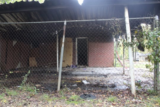 The carport of a home where two dead people were found inside a burning car.