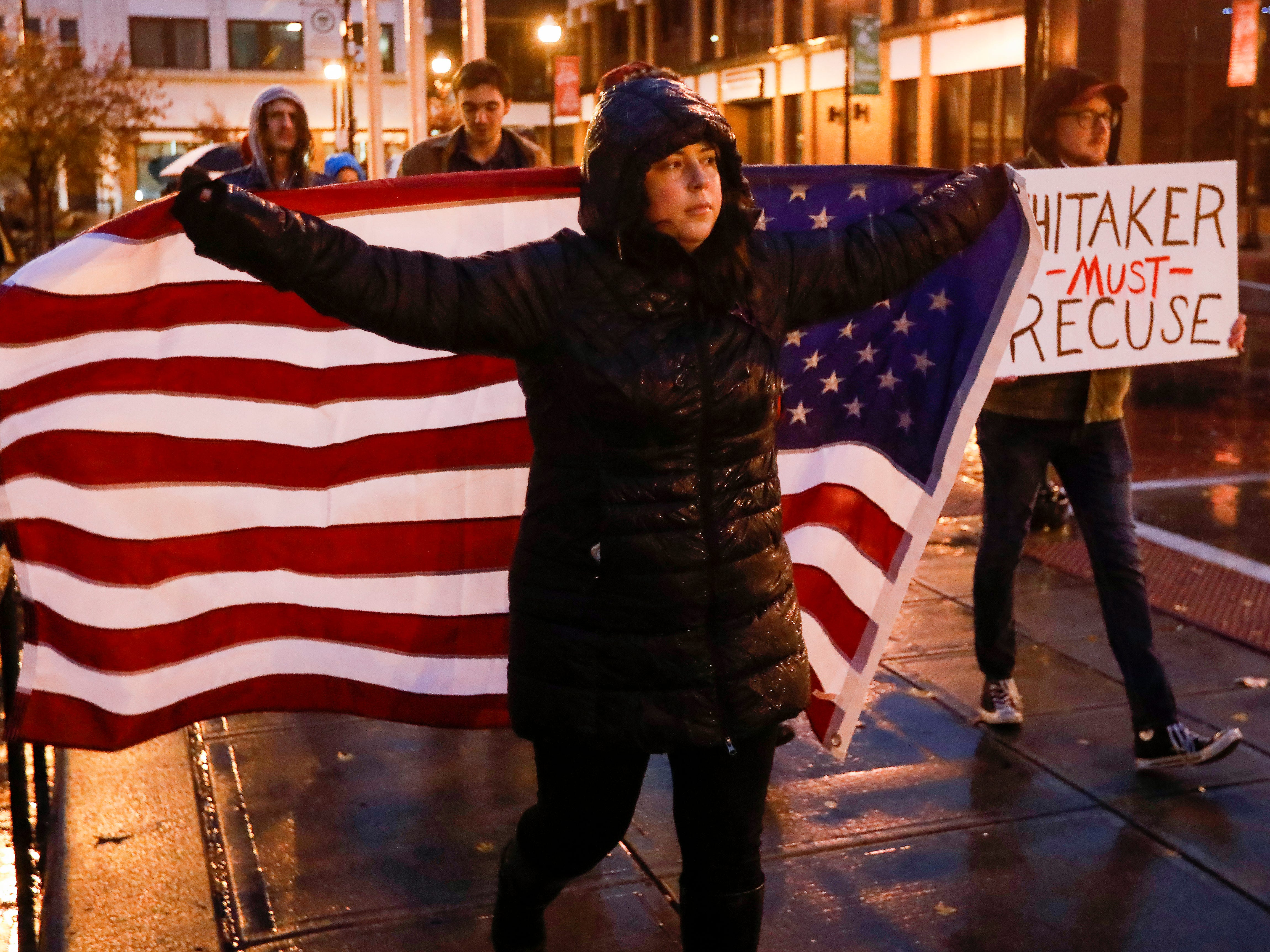 "Sheila Prost, of Springfield, carries a U.S. flag as she marches around Park Central Square on Thursday, Nov. 8, 2018. Prost said: ""I'm here to protest and demand that the new attorney general recuse himself from the Mueller investigation."""