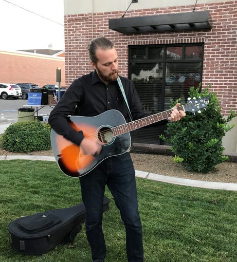 Kenneth Charette provides acoustical accompaniment for demonstrators during a protest in St. George November 8, 2018.