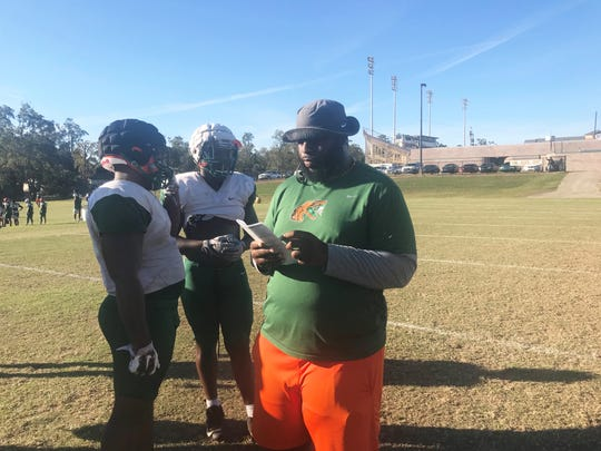 FAMU offensive coordinator/offensive line coach Alex Jackson reviews the play sheet during practice.