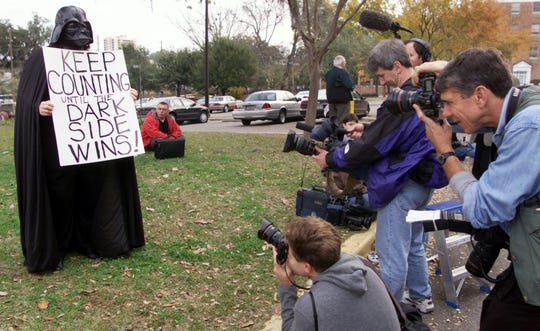 Photographers take pictures of Kim Watson, who is  dressed as Darth Vader to protest outside the Leon County Public Library, while the recount of the Miami-Dade under vote is taking place inside on Saturday in Tallahassee.