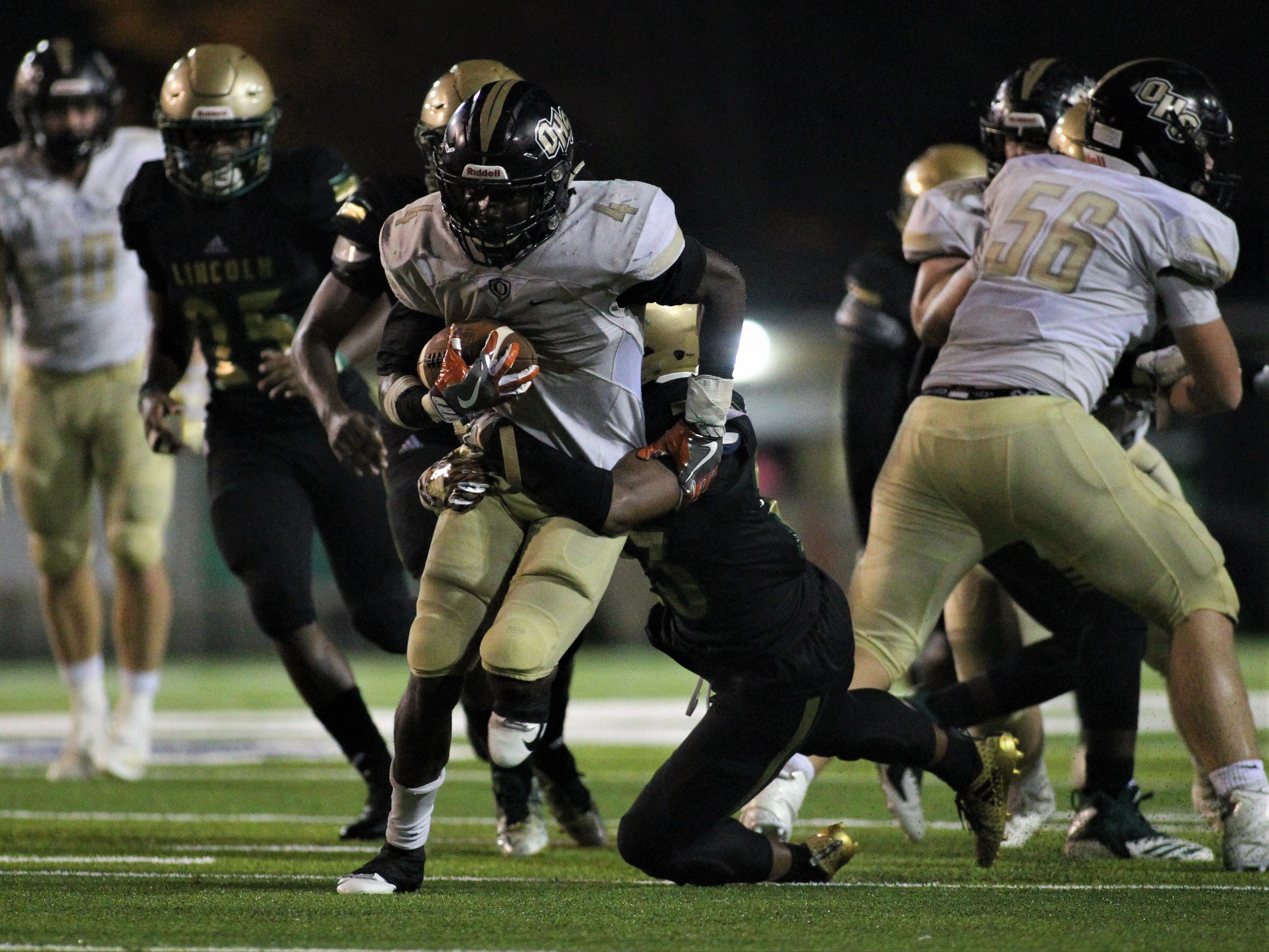 Oakleaf running back Keshawn King is tackled from behind by Lincoln's Daniel Newman, and Lincoln beat Oakleaf 38-31 in three overtime periods during a Region 1-7A quarterfinal Thursday night at Gene Cox Stadium.