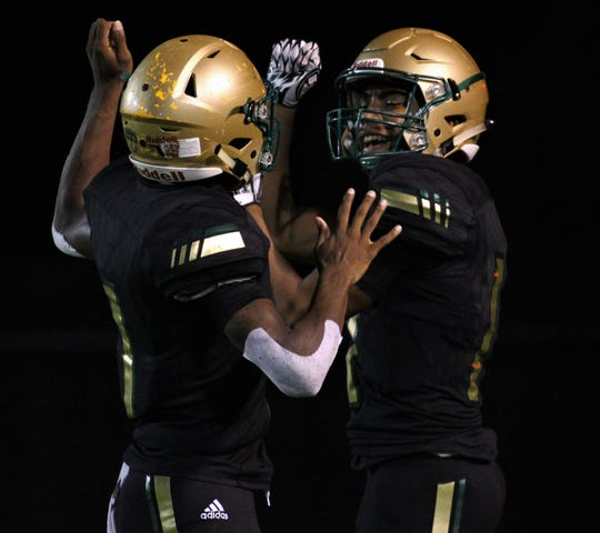 Lincoln's Marko Skarica celebrates a touchdown catch with quarterback Chris Beard (1) as Lincoln beat Oakleaf 38-31 in three overtime periods during a Region 1-7A quarterfinal Thursday night at Gene Cox Stadium.