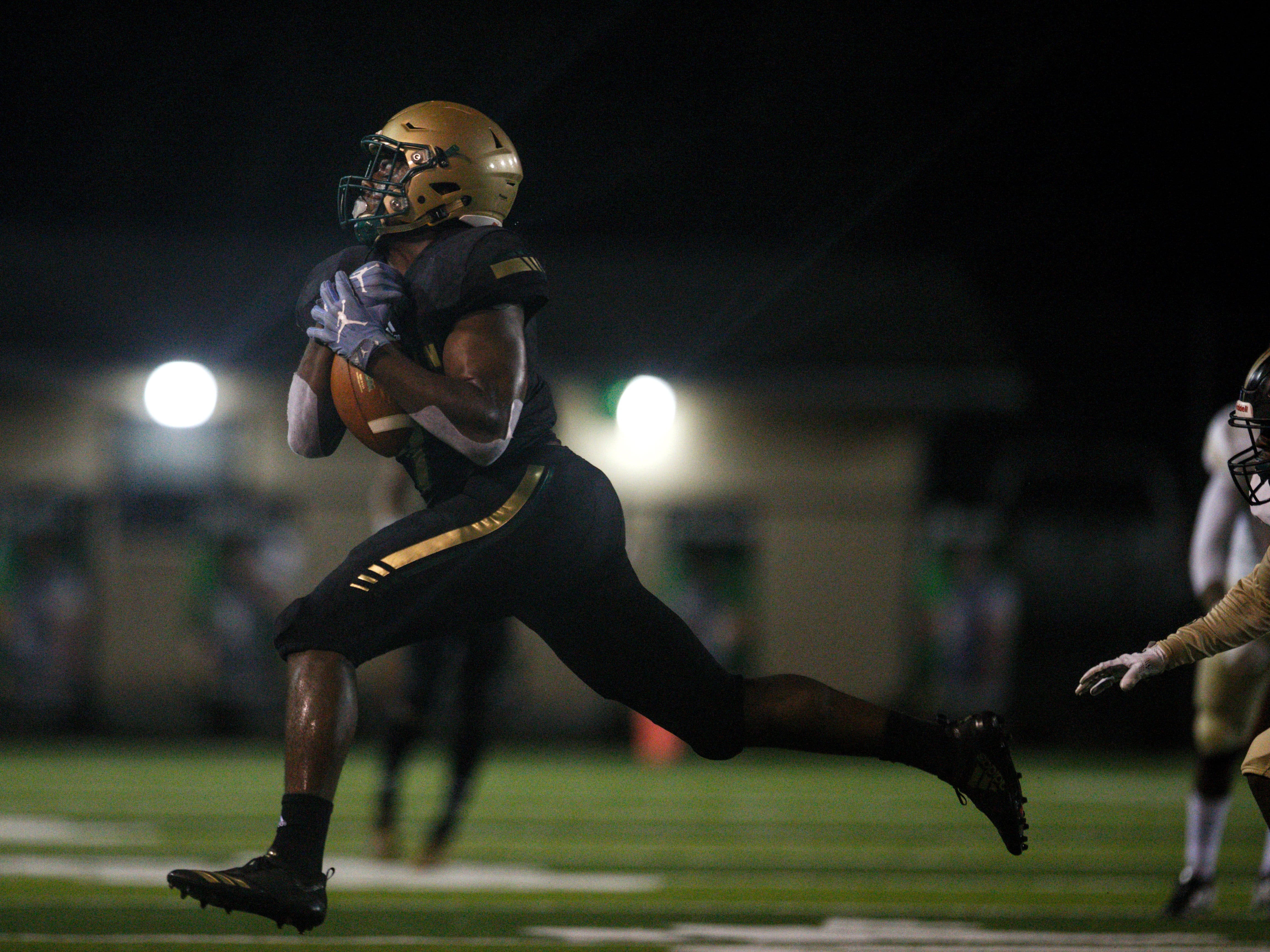 Lincoln's Kamari Morales hauls in a catch on the run as Lincoln beat Oakleaf 38-31 in three overtime periods in a  Region 1-7A quarterfinal Thursday night at Gene Cox Stadium.