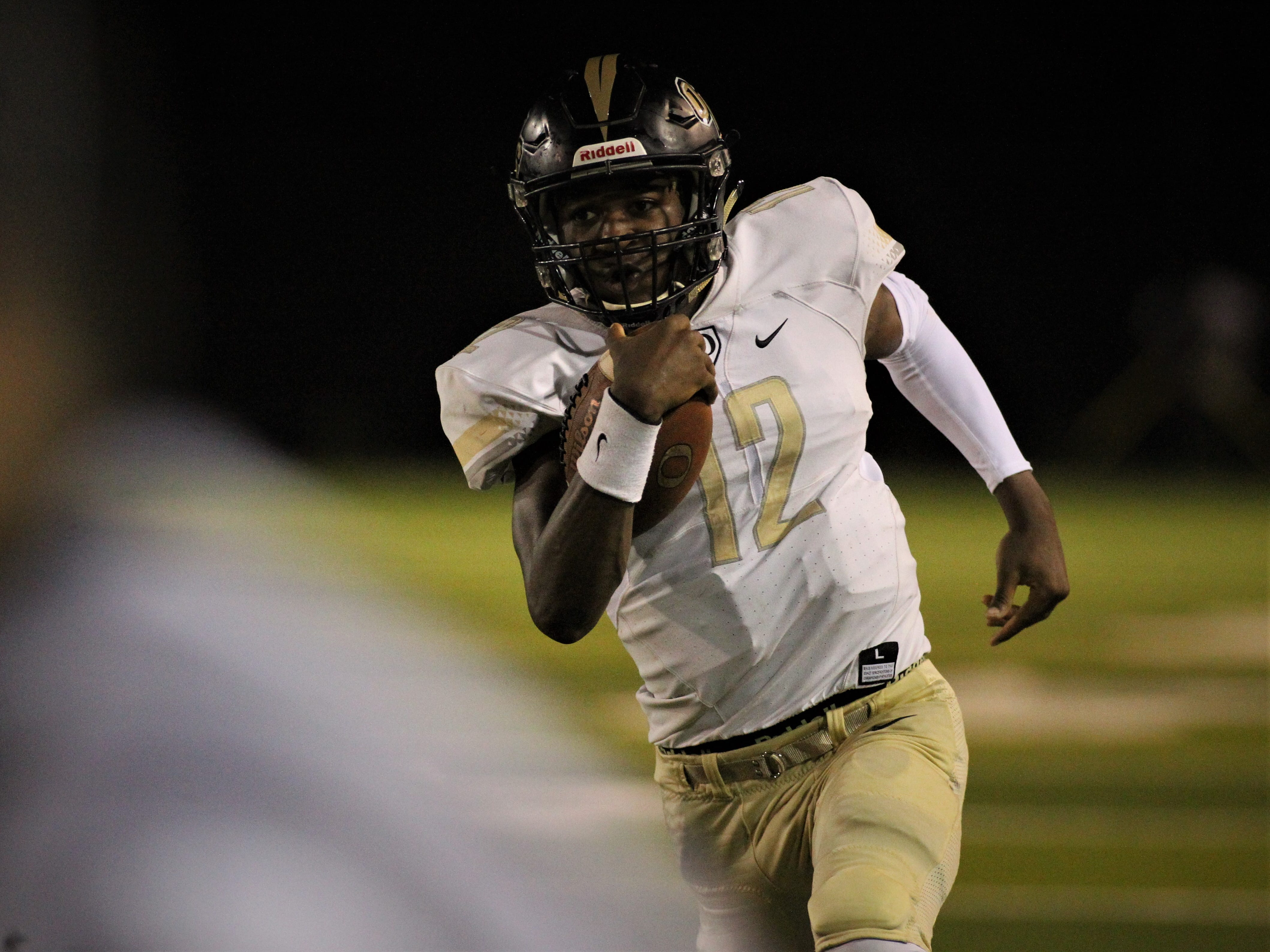 Oakleaf quarterback Walter Simmons III runs for yards as Lincoln beat Oakleaf 38-31 in three overtime periods during a Region 1-7A quarterfinal Thursday night at Gene Cox Stadium.