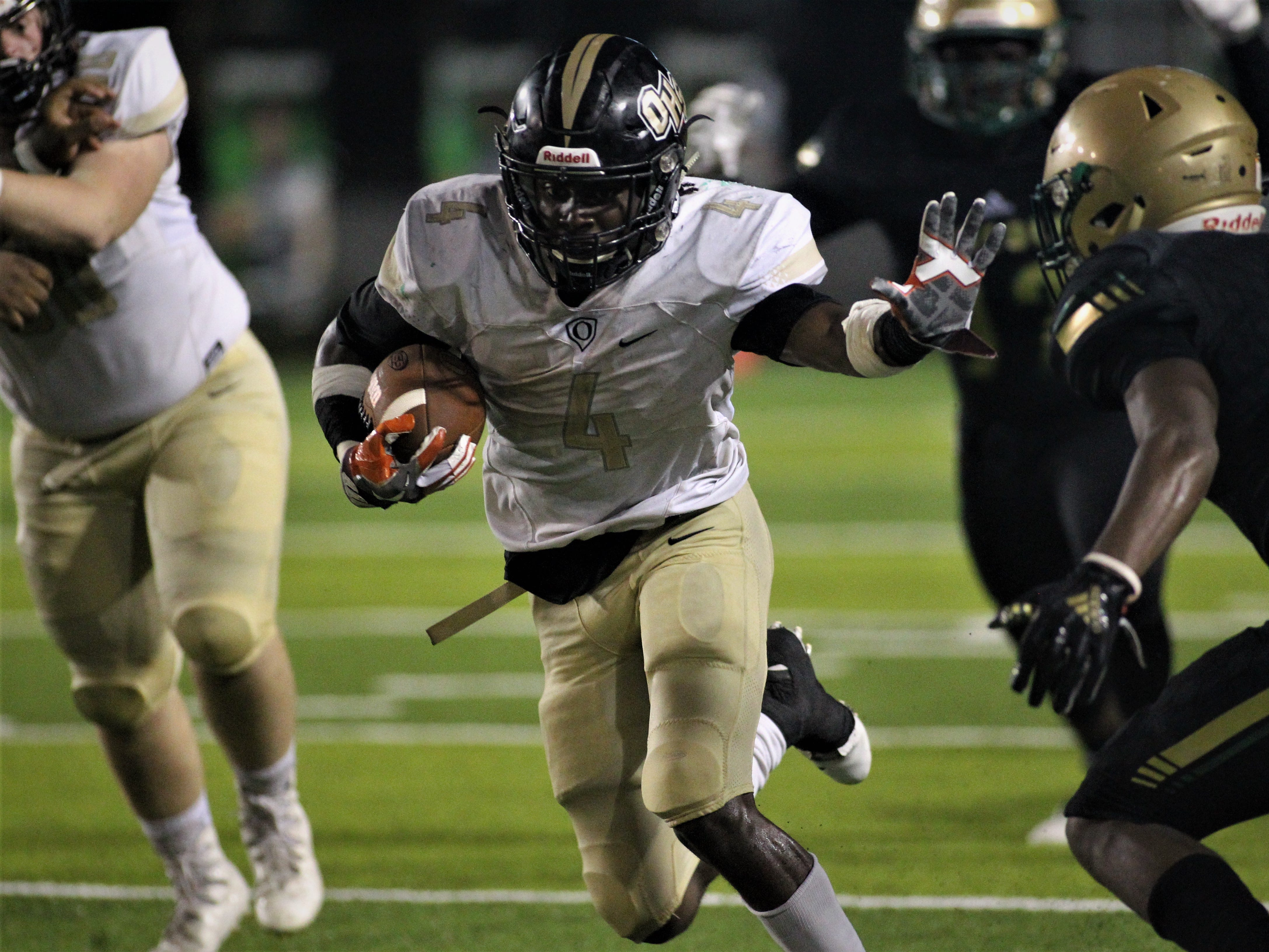 Oakleaf running back Keshawn King prepares to stiff arm a defender, but Lincoln beat Oakleaf 38-31 in three overtime periods during a Region 1-7A quarterfinal Thursday night at Gene Cox Stadium.