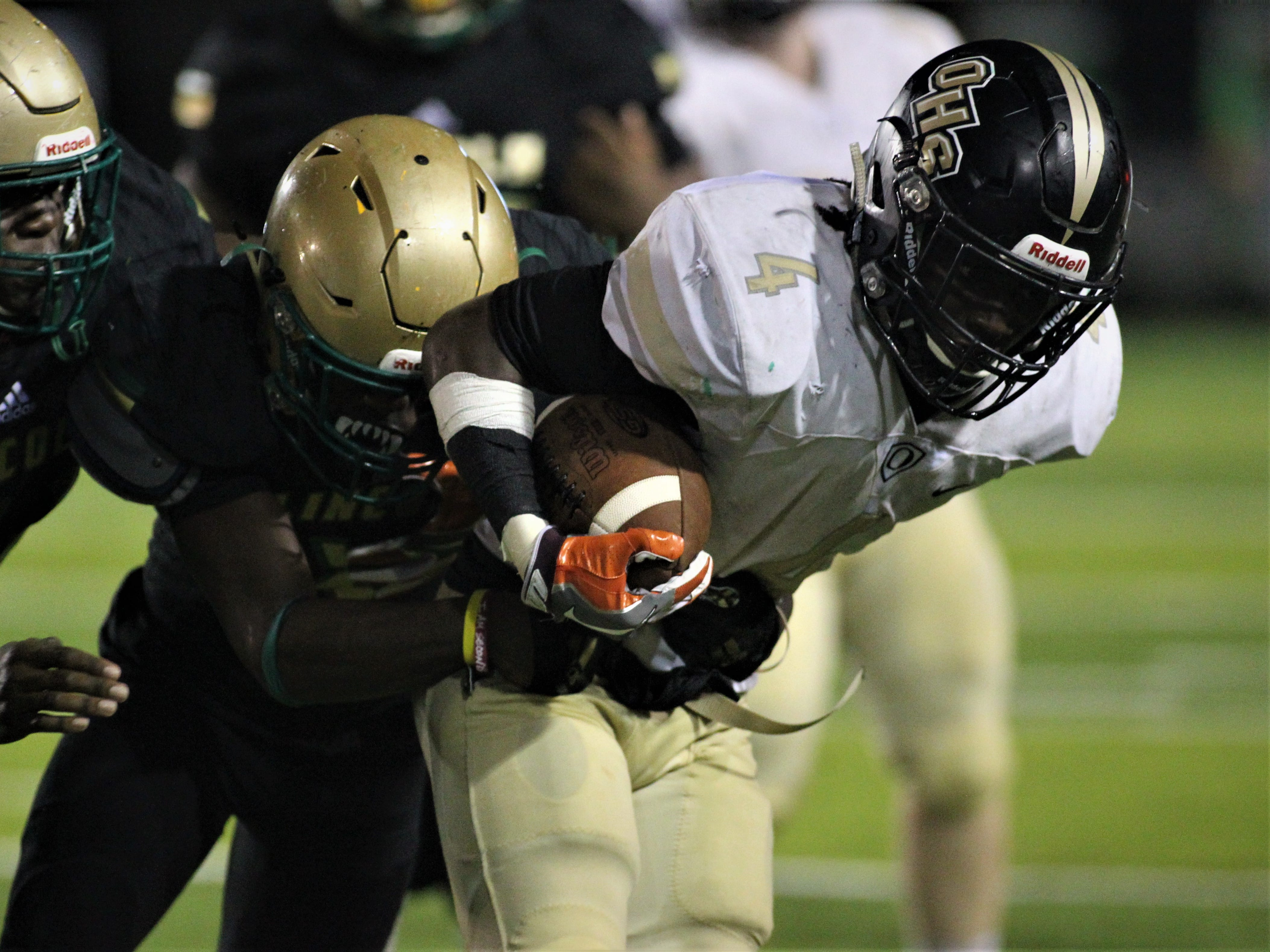 Oakleaf running back Keshawn King is dragged down by Lincoln defenders as the Trojans beat Oakleaf 38-31 in three overtime periods during a Region 1-7A quarterfinal Thursday night at Gene Cox Stadium.