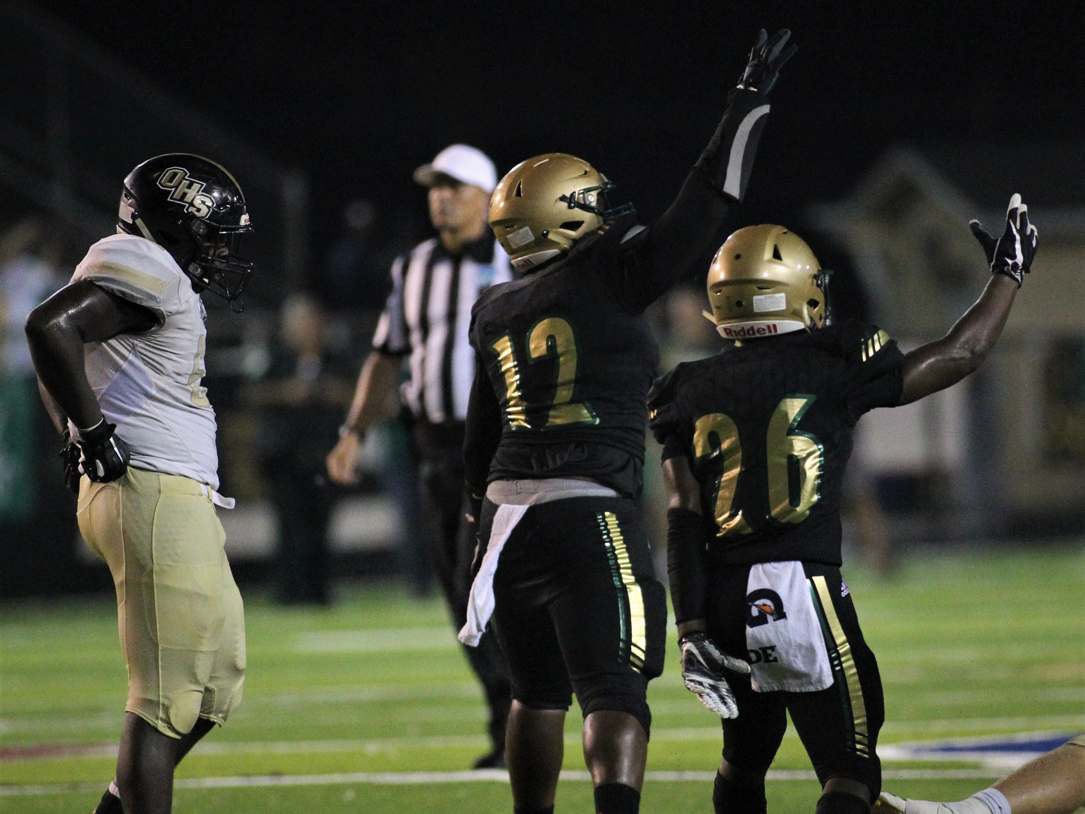 Lincoln's Isaiah Hendley (26) and Jourdan Jones (12) celebrate a fourth-down stop and a turnover-on-downs, as Lincoln beat Oakleaf 38-31 in three overtime periods during a Region 1-7A quarterfinal Thursday night at Gene Cox Stadium.