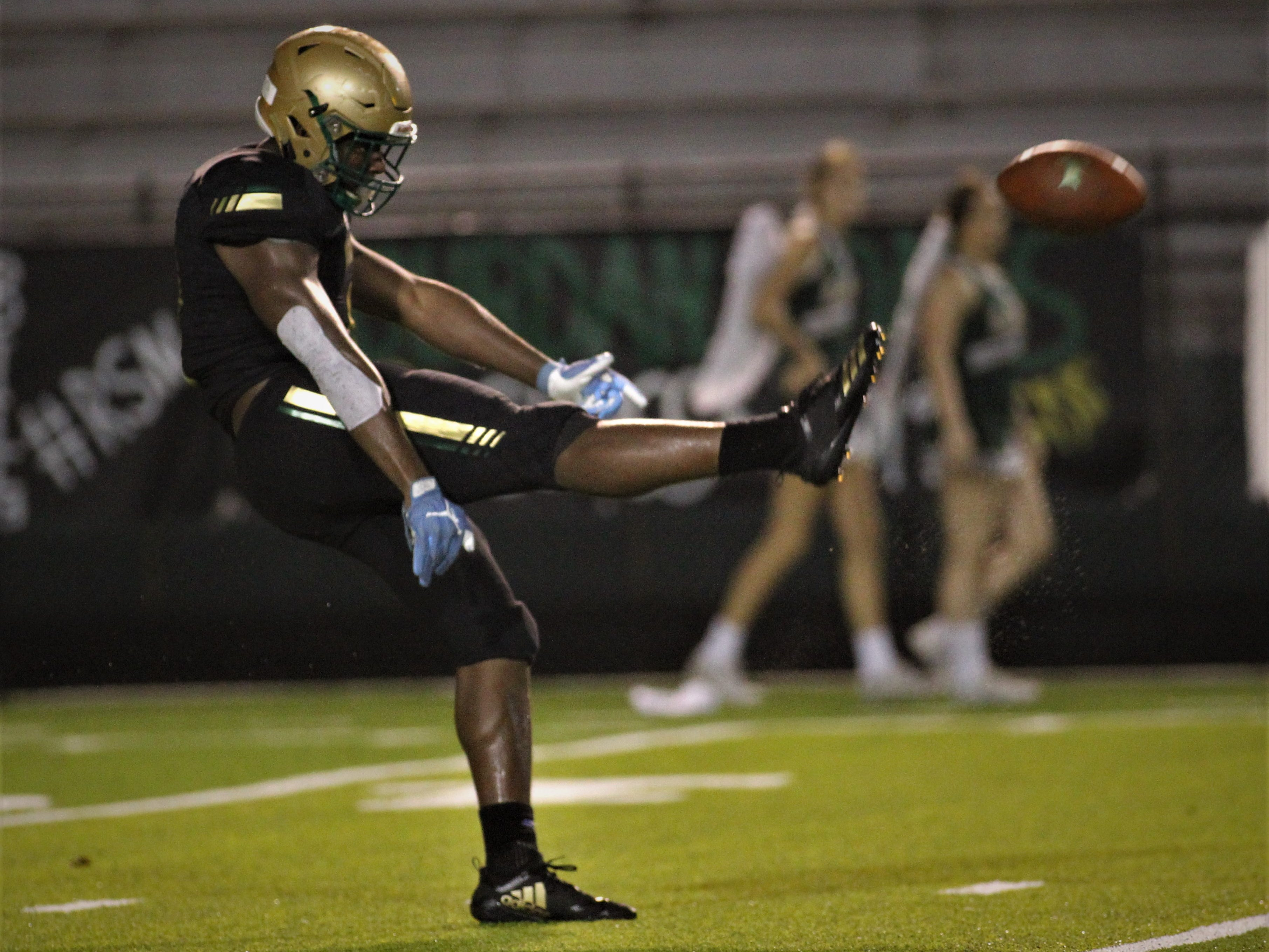Lincoln's Kamari Morales gets off a punt as Lincoln beat Oakleaf 38-31 in three overtime periods during a Region 1-7A quarterfinal Thursday night at Gene Cox Stadium.