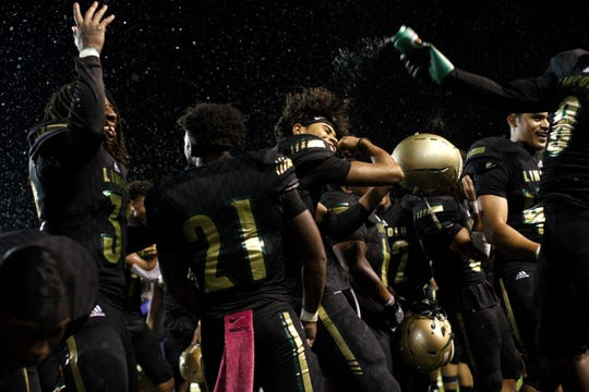 Lincoln players celebrate after beating Oakleaf 38-31 in three overtime periods in a  Region 1-7A quarterfinal Thursday night at Gene Cox Stadium.