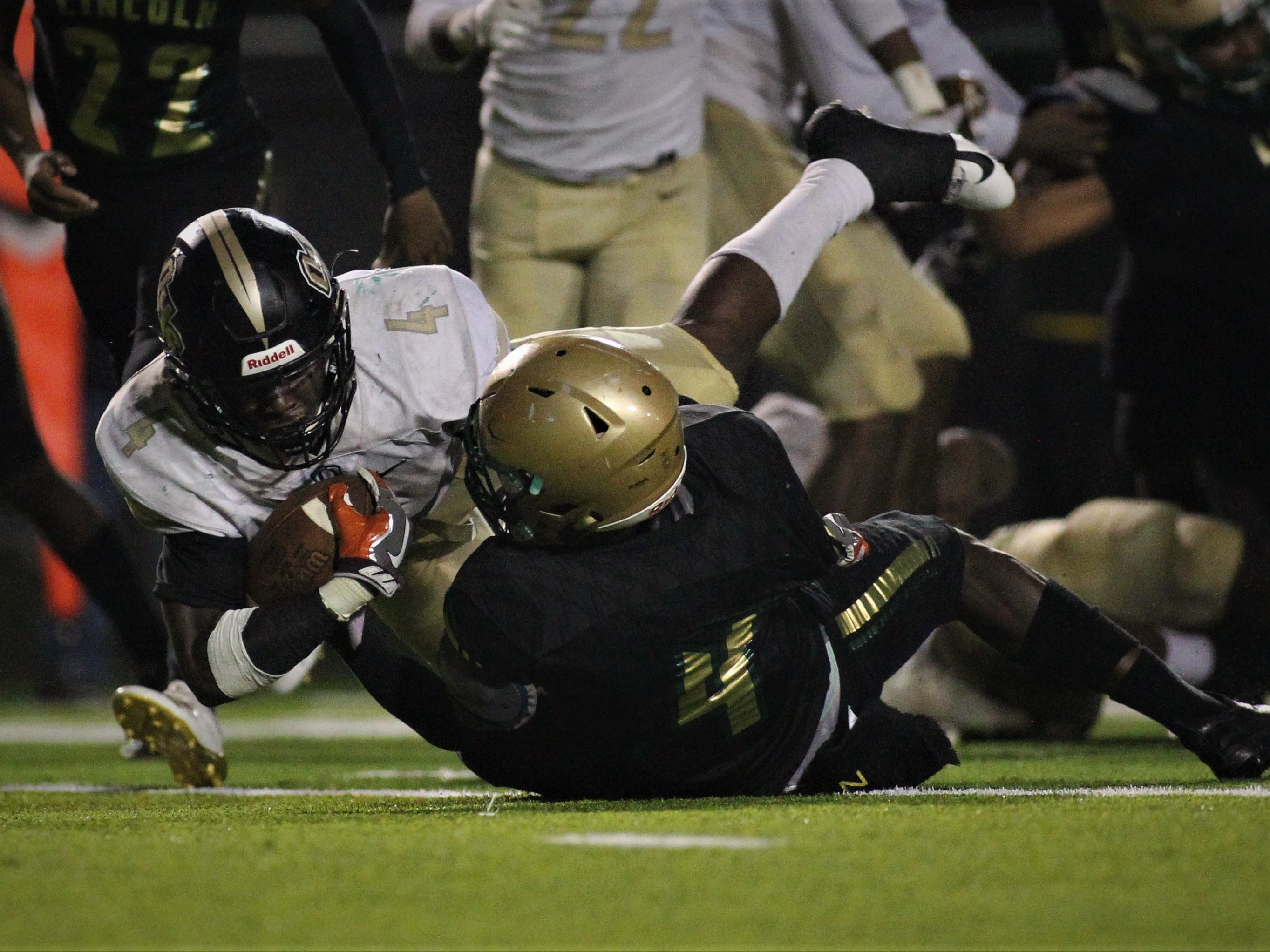 Oakleaf running back Keshawn King powers through Lincoln safety Jalen Glaze for a one-yard touchdown, but Lincoln beat Oakleaf 38-31 in three overtime periods during a Region 1-7A quarterfinal Thursday night at Gene Cox Stadium.