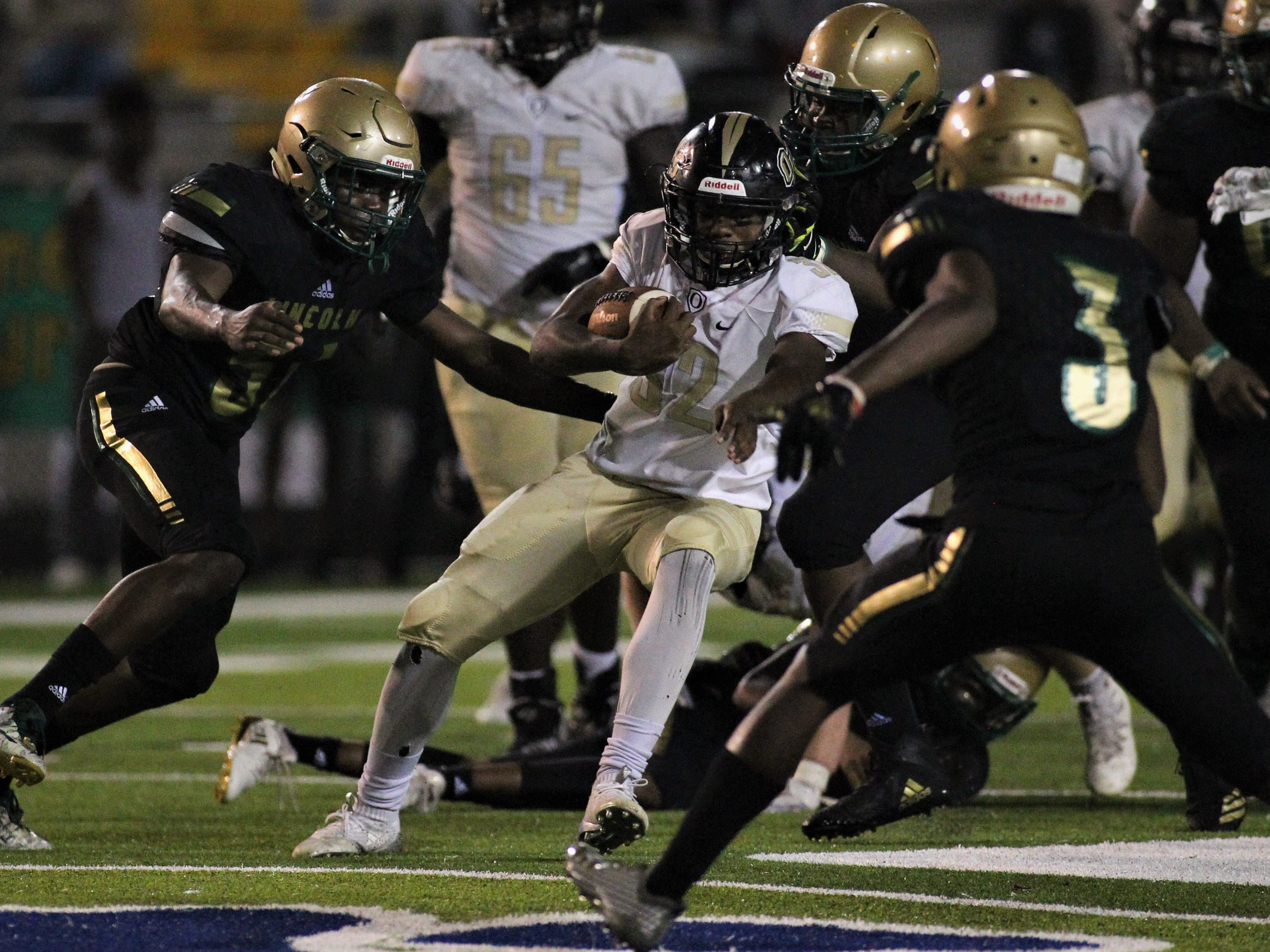 Oakleaf running back Adrian Gray is met by Lincoln defenders as the Trojans beat Oakleaf 38-31 in three overtime periods during a Region 1-7A quarterfinal Thursday night at Gene Cox Stadium.