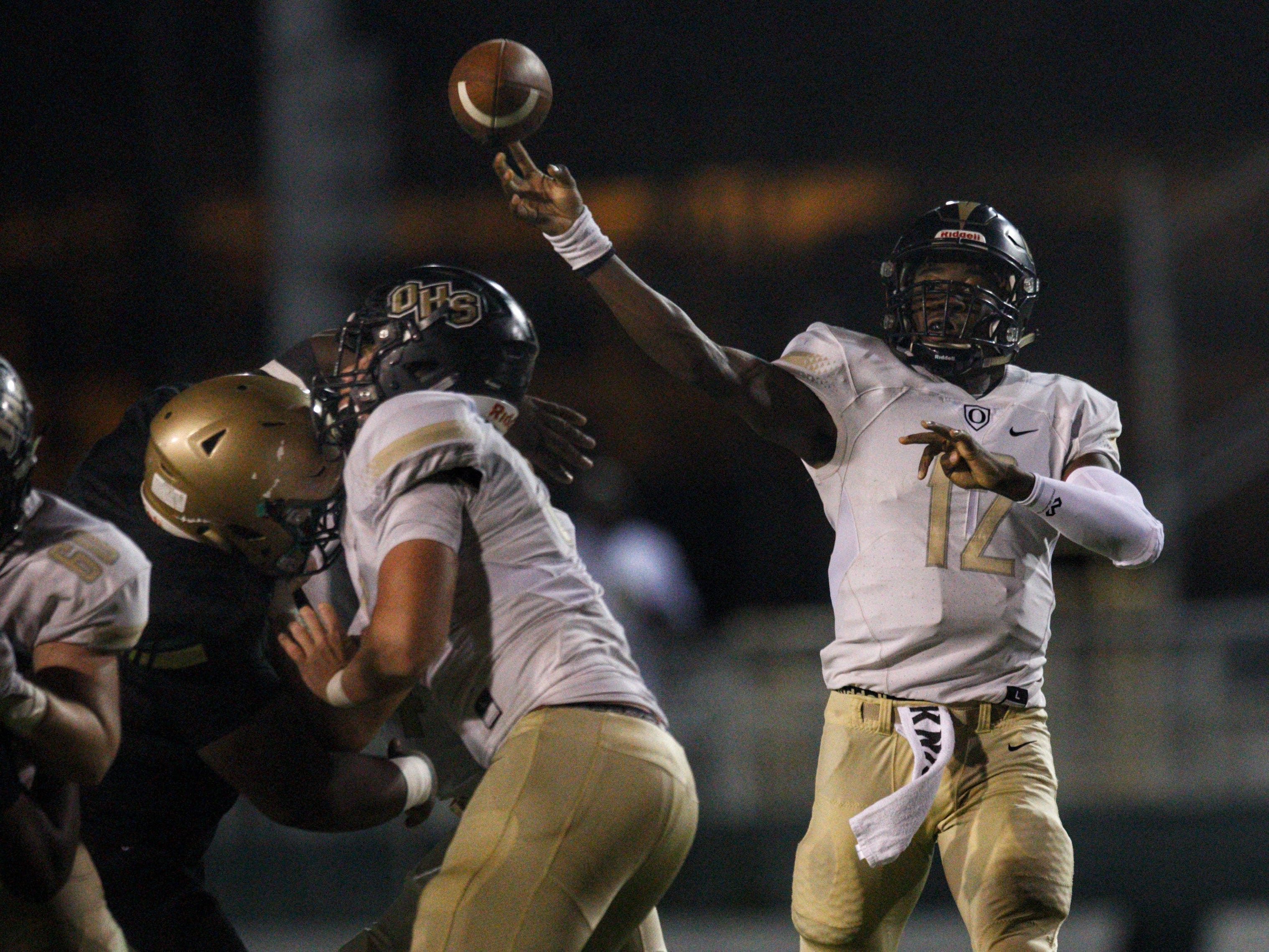 Oakleaf quarterback Walter Simmons III throws a pass as Lincoln beat Oakleaf 38-31 in three overtime periods in a  Region 1-7A quarterfinal Thursday night at Gene Cox Stadium.