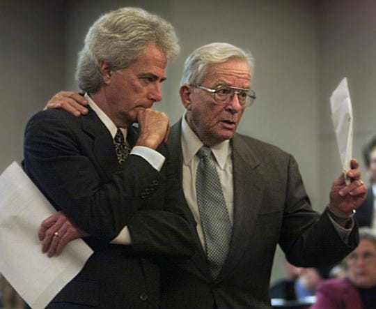 Dexter Douglass, right, puts his arm around Barry Richard during a hearing about the 2000 election.