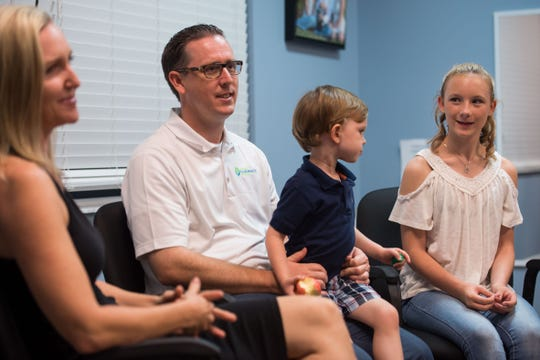 "Chiropractor Brian Moriarty (second from left) posted on the ""Stuart Moms"" Facebook page about his stepdaughter, Paige Beams (right), 13, being relentlessly bullied at school, which concerned follow parent and photographer Lindsey Potter (left). The three talk Monday, Nov. 5, 2018, at Loving Chiropractic of Stuart."