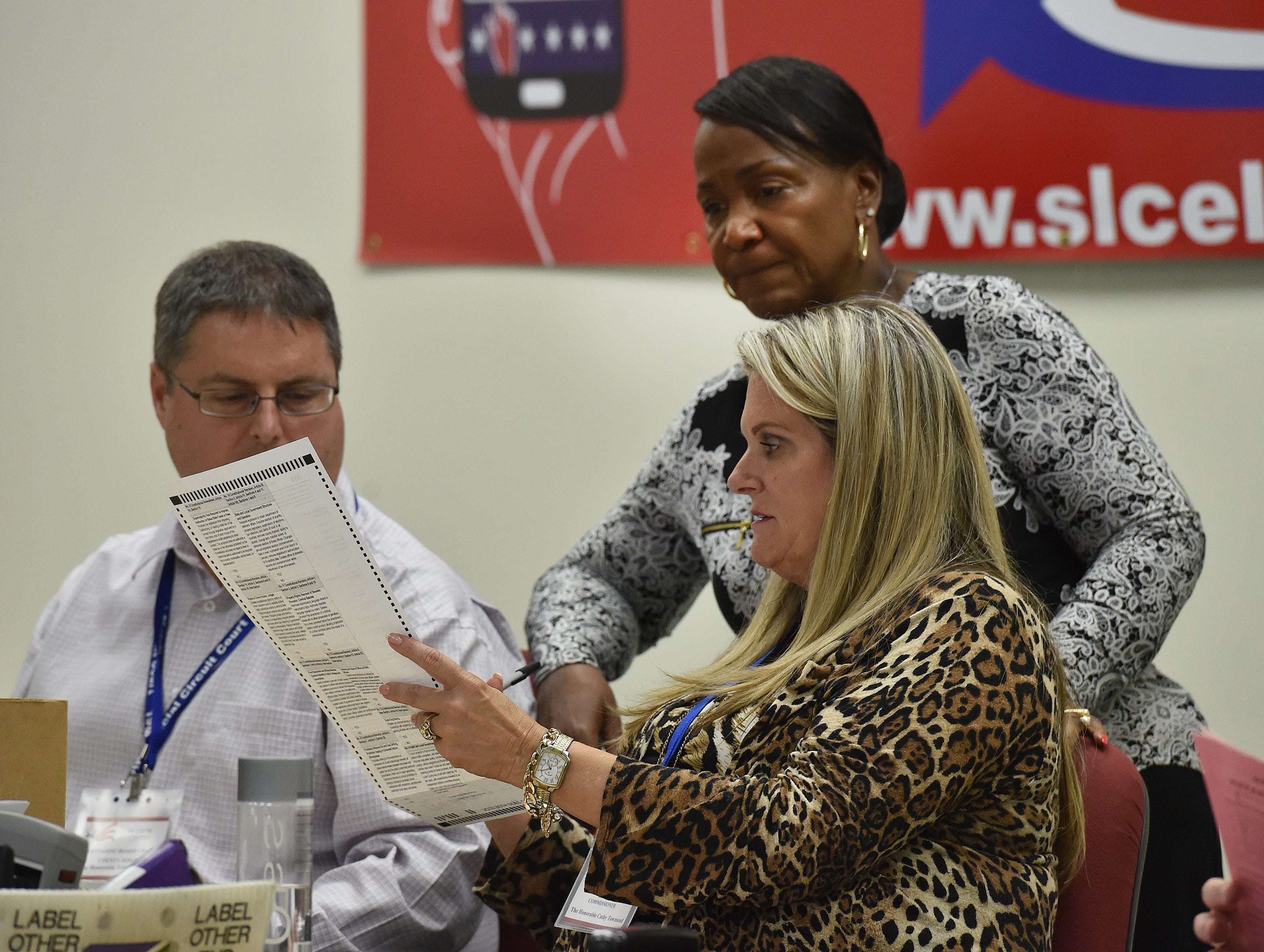 Gertrude Walker (top), Supervisor of Elections for St. Lucie County, looks over an accepted ballot with canvassing board members County Judge Edmond Alonzo (left) and St. Lucie County Commissioner Cathy Townsend as they sort through provisional ballots on Thursday, Nov. 8, 2018, at their office in Fort Pierce. Out of 122 provisional ballots, 42 were accepted by the canvassing board, according to Gertrude Walker.