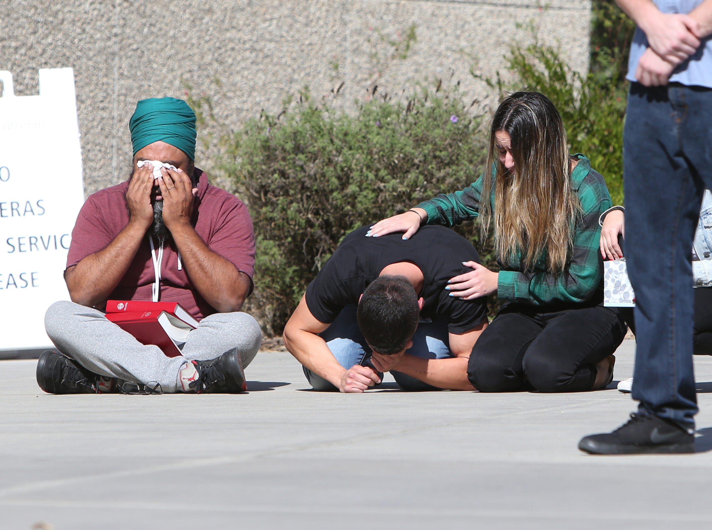 Cal Lutheran's Dr. Rahuldeep Gill (left) wipes away tears as one of the students break down during a service Thursday held for the victims of the Borderline Bar Borderline Bar & Grill shooting.