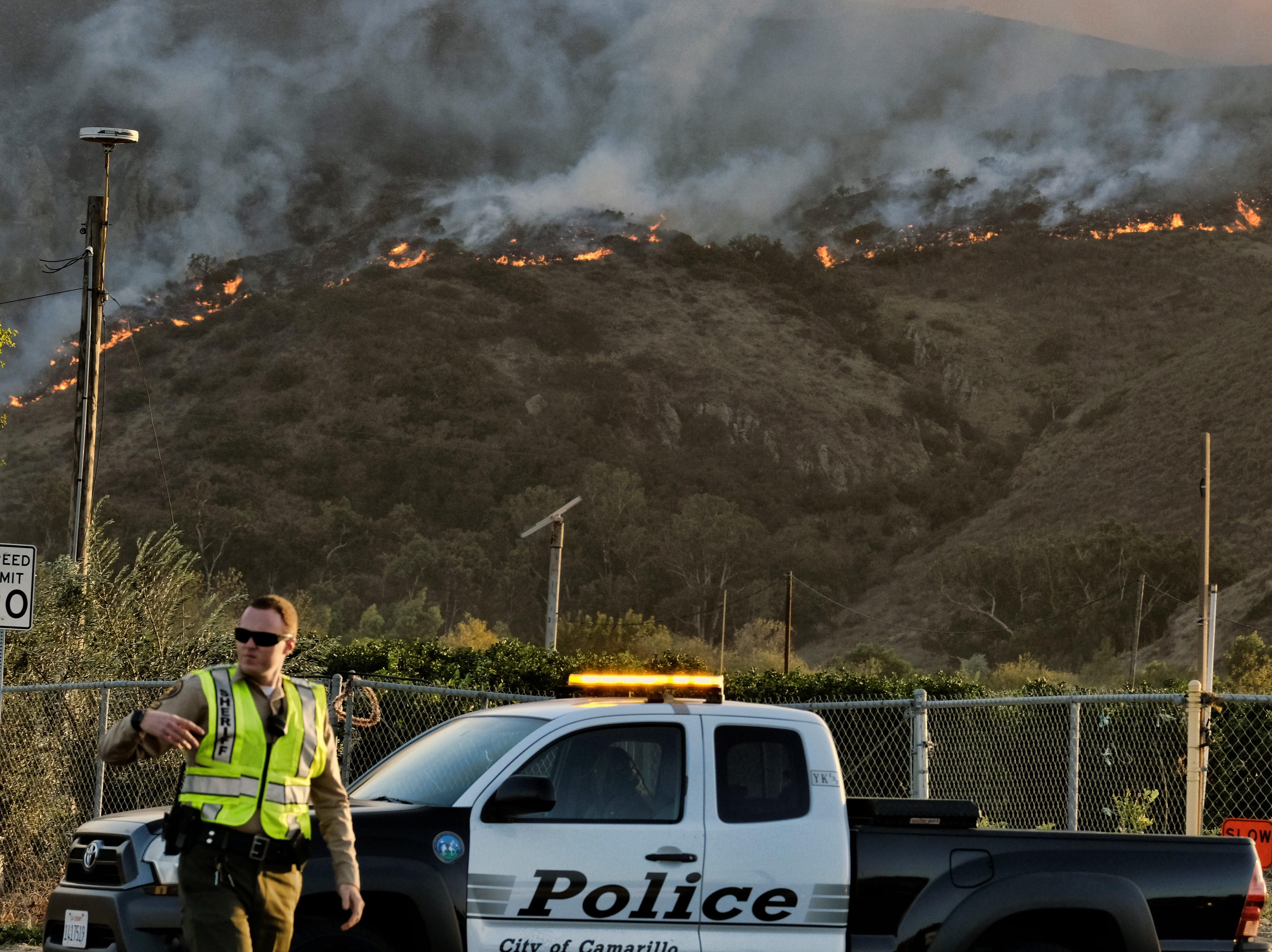 A police officer directs traffic at a checkpoint in front of an advancing wildfire Thursday near Newbury Park. The Hill Fire led to evacuations as it raced from the Santa Rosa Valley toward CSU Channel Islands.