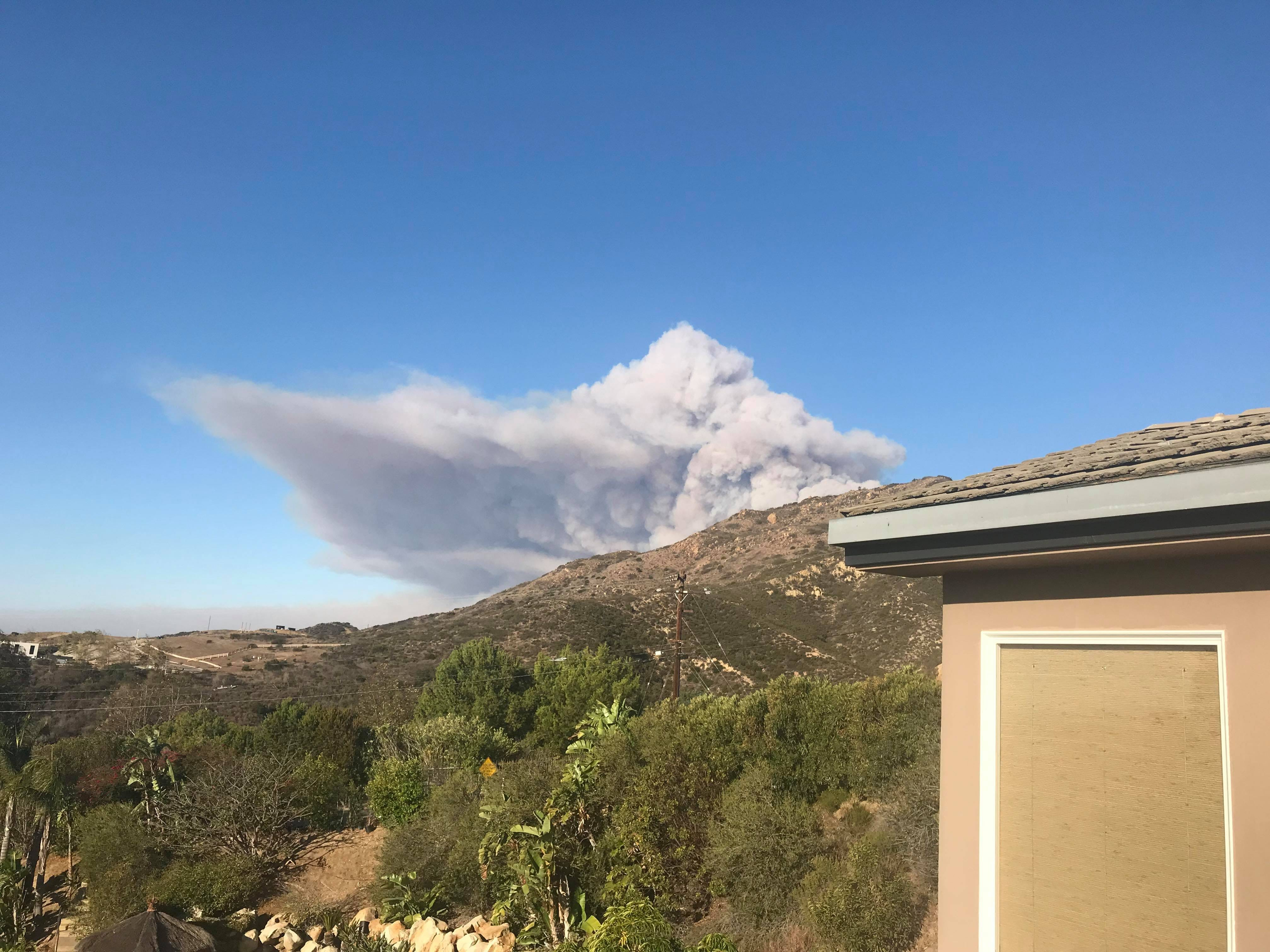 Smoke can be seen from a home in eastern Malibu on Carbon Canyon Road as the Woolsey Fire burns on Friday.