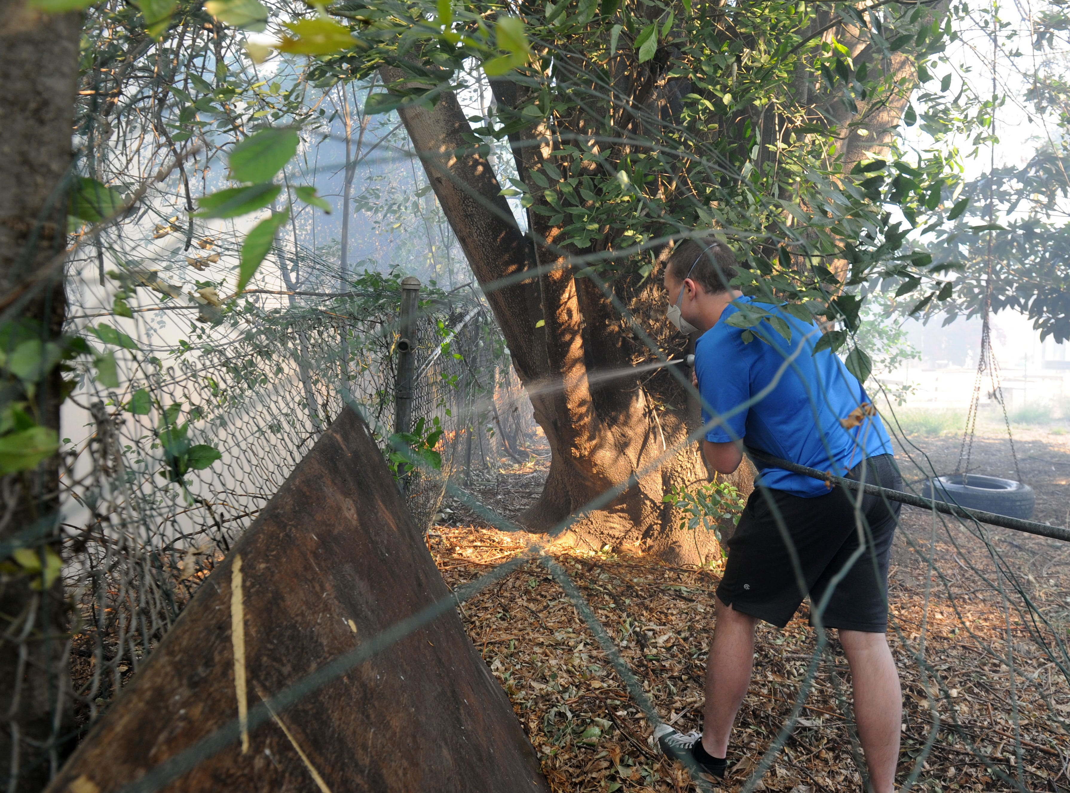 Ryan Mackenzie helps with the small flames near his home at Erbes Road and El Monte Drive in Thousand Oaks.