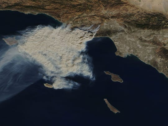 In this image provided by NASA's Earth Observing System Data and Information System (EOSDIS), smoke from the Woolsey and Hill Fires can seen on the Southern California coast.