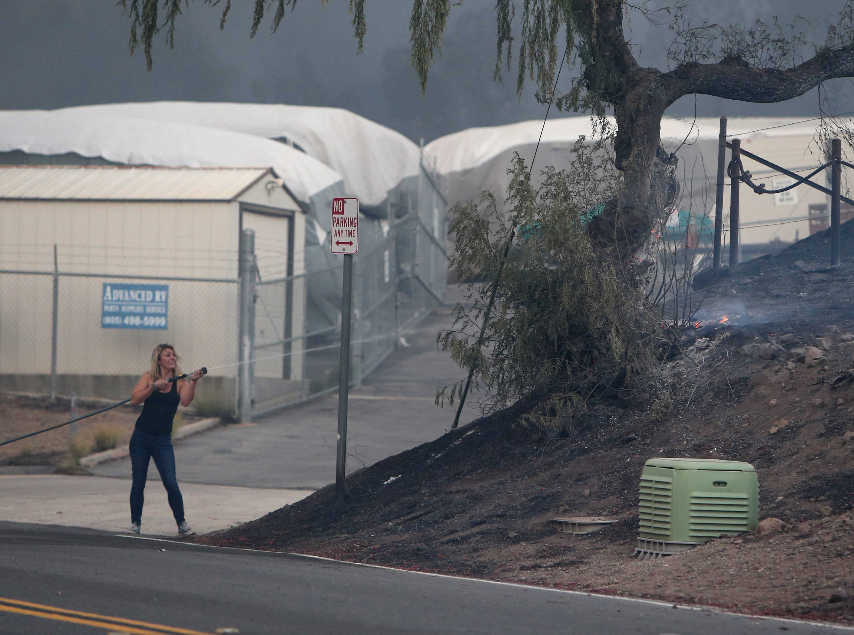 Shelby Farkas puts out a small brush fire Thursday with a garden hose she got from her boyfriend's mother at a mobile home just off Old Conejo Road in Newbury Park.