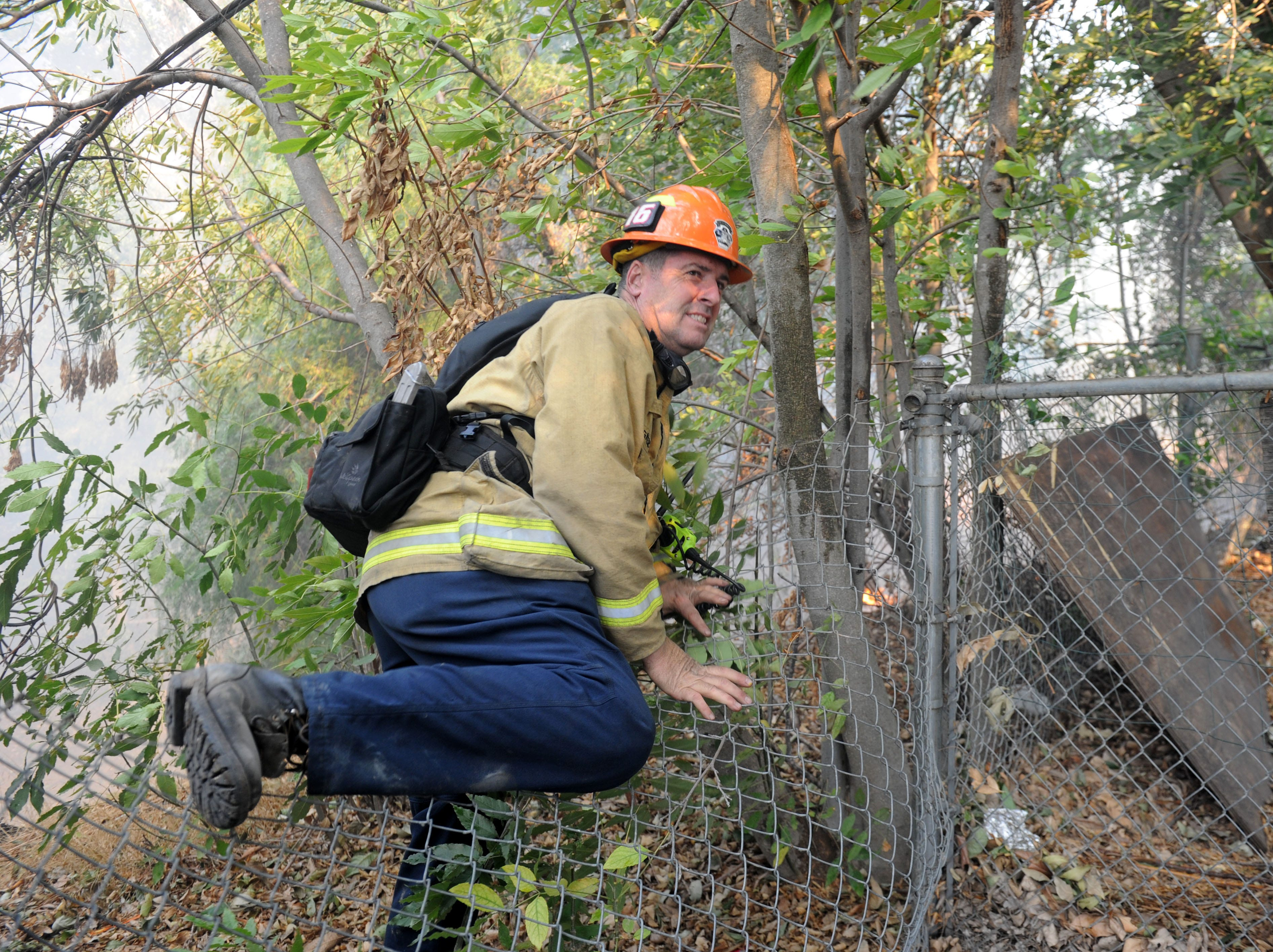 A firefighter jumps a fence that had flames at Erbes Road and El Monte Drive in Thousand Oaks.