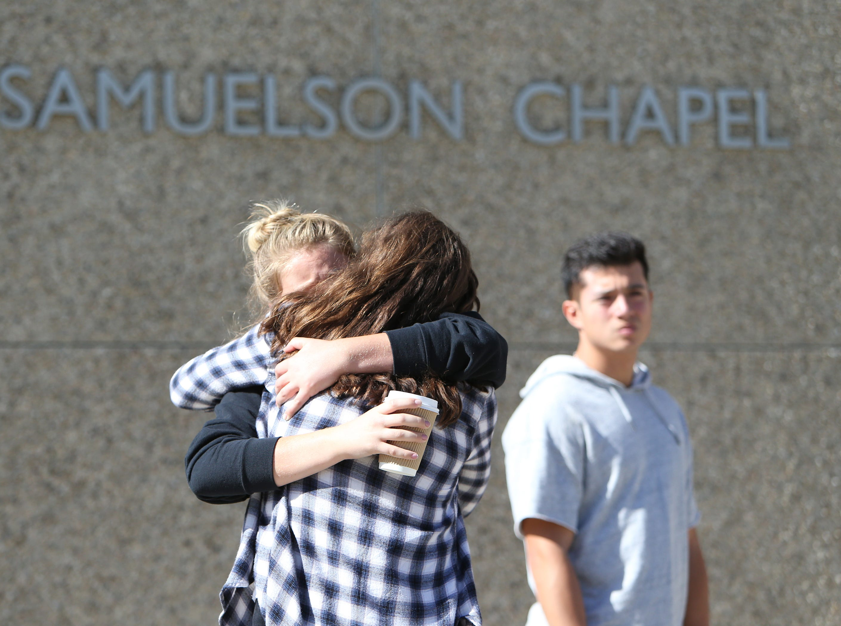 Cal Lutheran students console each other before Thursday's service for the victims of the Borderline Bar Borderline Bar & Grill shooting.