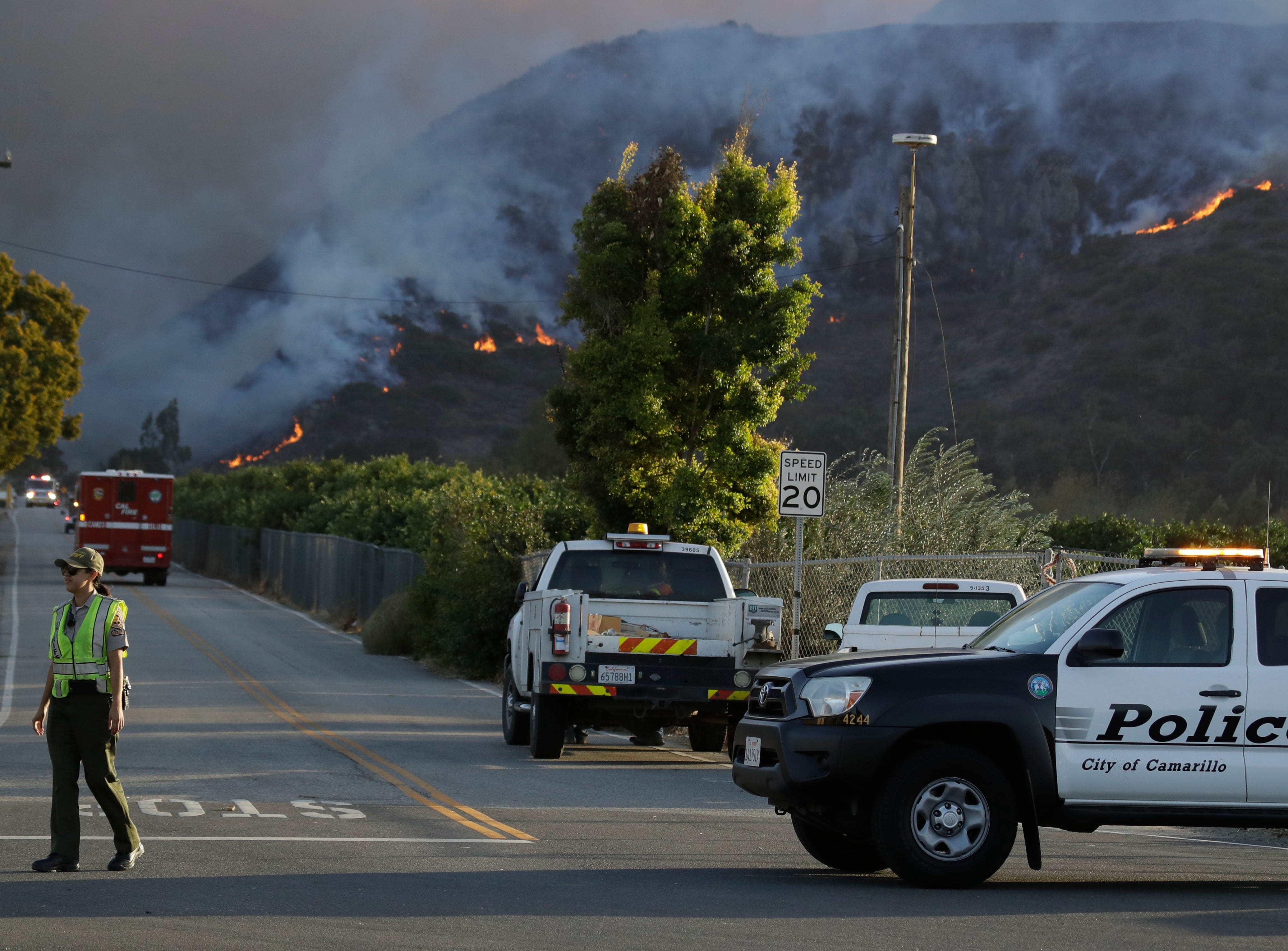 A police officer staffs a checkpoint in front of an advancing wildfire Thursday near Newbury Park. The Hill Fire led to evacuations as it raced from the Santa Rosa Valley toward CSU Channel Islands.