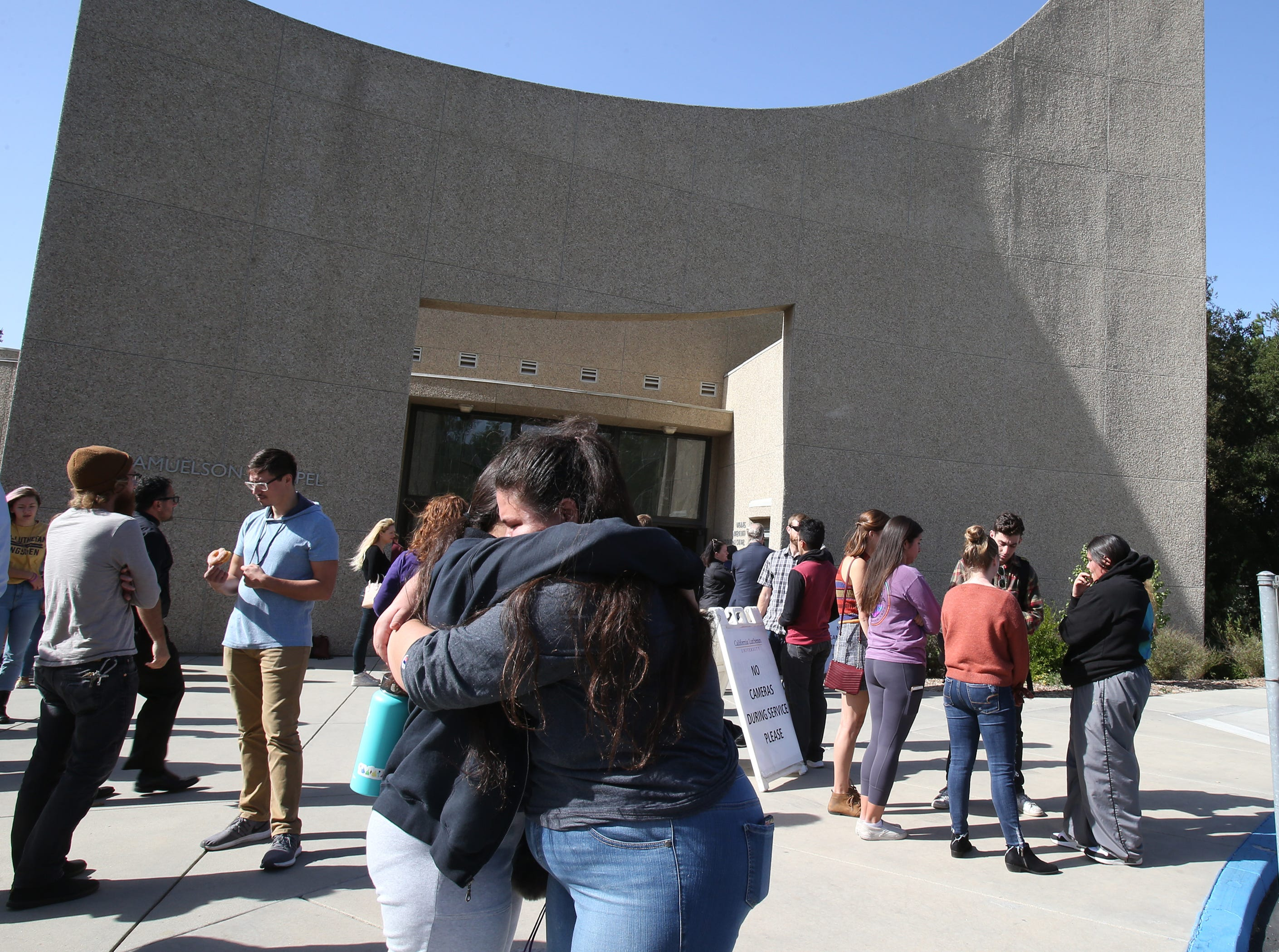 Cal Lutheran students Emmalee Villafana and Bianca Akbiyik hug each other after the service Thursday for the victims of the Borderline Bar Borderline Bar & Grill shooting.