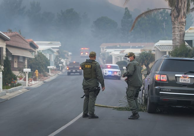 Ventura County sheriff's officers work on evacuating residents from a mobile home park off Old Conejo Road in Newbury Park.
