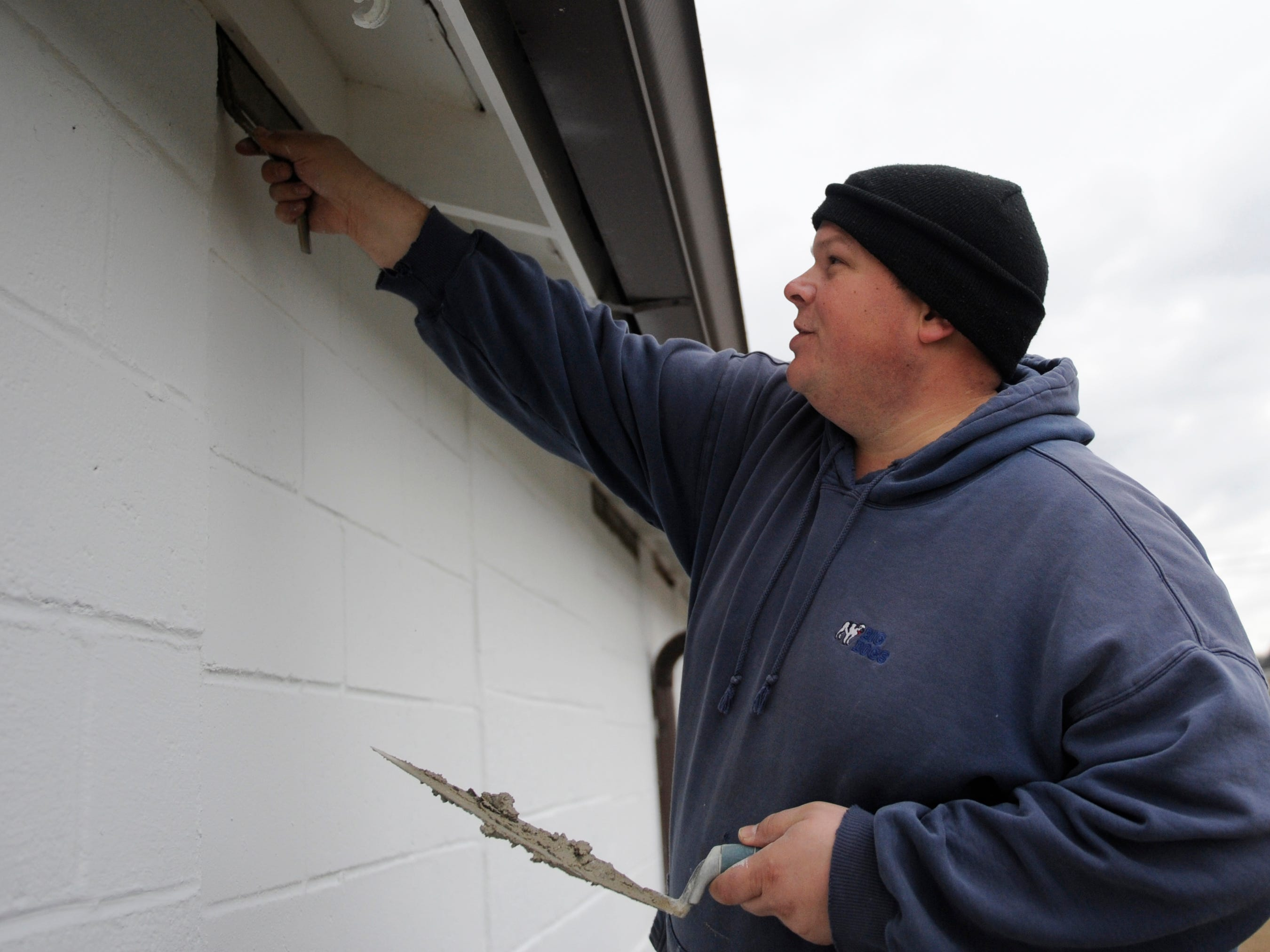 Steven England, Vineland Home Depot assistant manager and community captain, works on patching a wall with cement during a special building renovation event at Millville Army Airfield Museum.