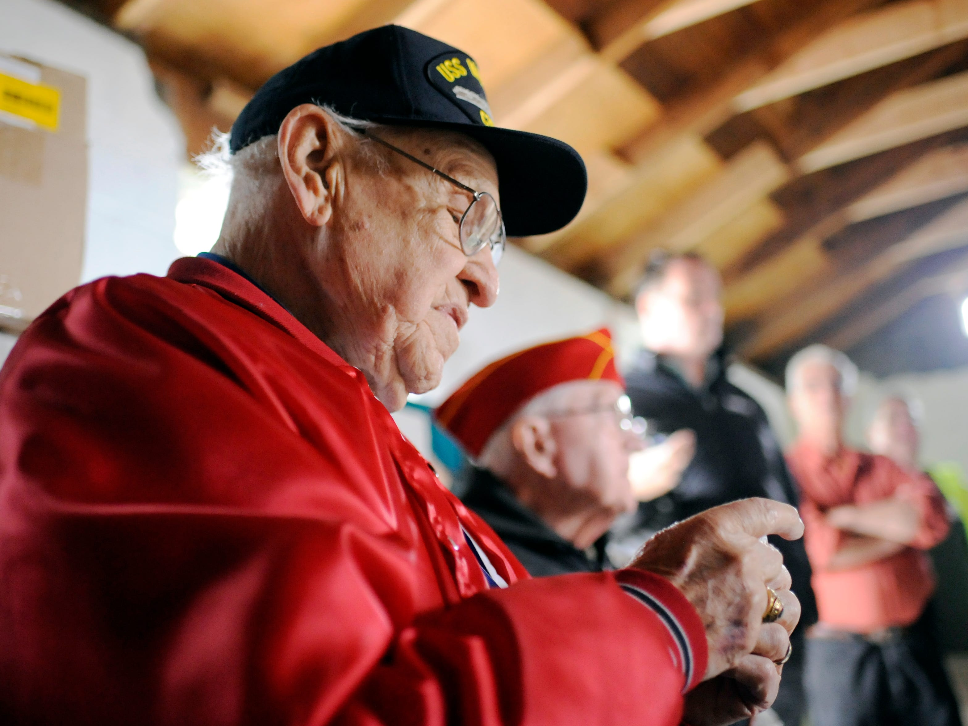 Owen Garrison, a 93-year-old WWII Navy Veteran and Millville Army Airfield Museum volunteer, looks at a special medal given to him by the Home Depot team during a building renovation event on Friday, November 9, 2018.