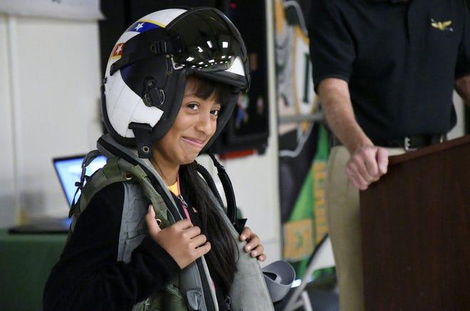 Ivanhoe Elementary School fifth-grader Joanna Arce Nunez, 10, tries on flight gear brought by Lt. Matthew McDonald during a presentation on Friday, November 9, 2018.