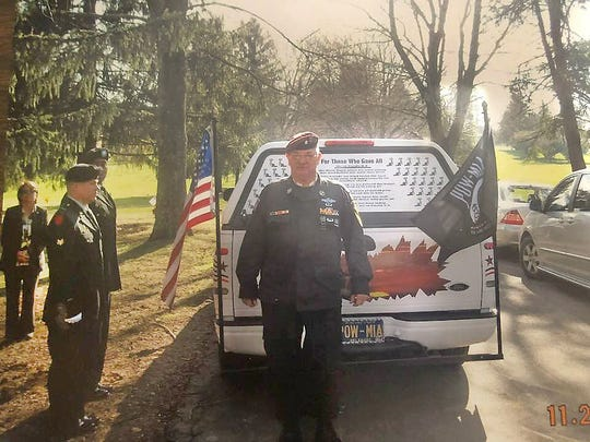 Wilmington veteran Ron Elliott stands by his customized truck after a funeral for a fellow veteran.