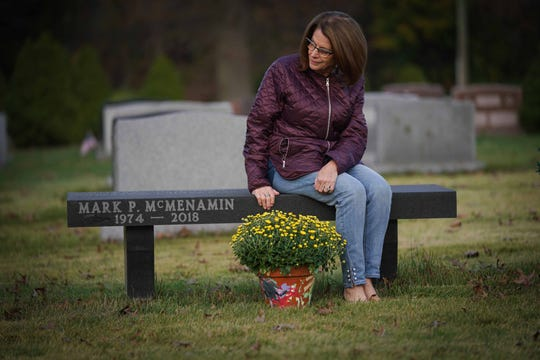 Paula DiSabatino Gorman sits on a memorial bench over the grave of her 42 year-old son Mark McMenamin who died last year when he crashed his truck into the Christina River.