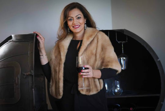 Shalini Sawhney wears a black long-sleeve jumpsuit with draped silhouette by Ralph Lauren in stretch jersey from Macy's; faux fur jacket from Vintage Aquamarine; and black booties from Enzo Angiolini.