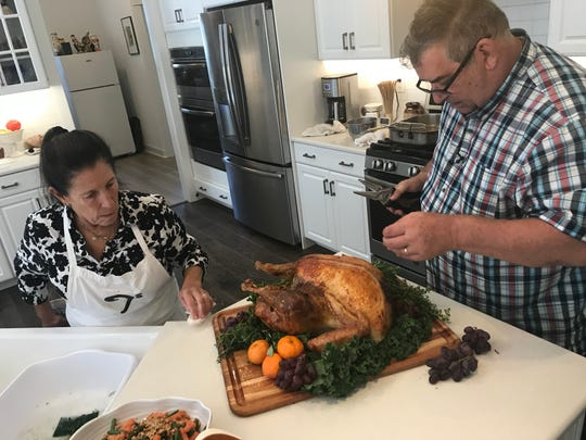 Rick Rodgers and his assistant, Sandy, garnish the turkey for a Thanksgiving feast he prepared in his Sussex County home.