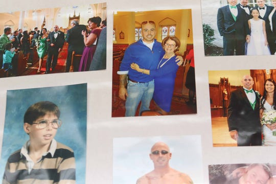 Family photographs of 42 year-old Mark McMenamin throughout his life remain on a memorial poster used at his funeral service.