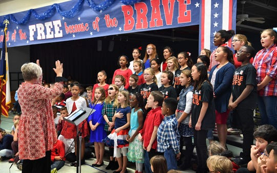 Tower Elementary music teacher Brenda Richison directs the Tower Treble Clefs as they sing an Armed Forces Salute Friday during a programing honoring service members and observing Veterans Day.
